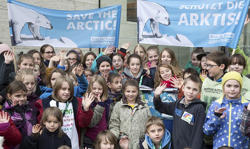 """Kinder winken am 10.04.2014 vor dem Auswärtigen Amt in Berlin und halten Plakate mit der Aufschrift """"Schützt die Arktis"""". Mit dieser Aktion setzen sich 60 junge Umweltschützer aus ganz Deutschland im Rahmen der Internationalen Arktis-Konferenz für den Schutz der Arktis ein. Die Kinder werden rund 52.000 Unterschriften überreichen, die sie für ein internationales Schutzgebiet gesammelt haben. Foto: Jörg Carstensen/dpa"""
